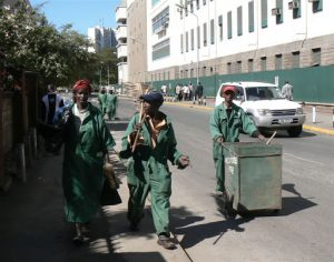 Nairobi downtown - street sweepers carry on their work even