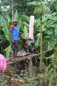 Sawing planks by hand along the village road in Marangu. As