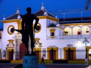 Seville in the evening outside the bullring with matador statue