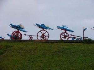 Artistic mechanical sculpture along the roadside - airplanes/birds and gears/wheels?