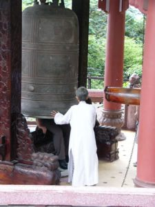Nha Trang - Ancient bronze bell at Buddhist shrine; tourists sit
