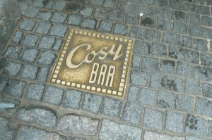Brass ground plate at the entry to Cosy Bar.
