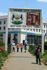 Harare: downtown business district - central park sign: Sunshine City