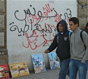 Two students in central Tunis walking past graffiti wall slogans.