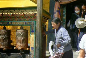 Tibet: Lhasa - Potala Palace - pilgrims and prayer wheels